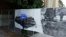 A fence with a banner showing old construction photos